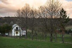 Μια όμορφη, άνετη άποψη σχετικά με ένα μικρό του χωριού σπίτι τομείς Στοκ Φωτογραφία