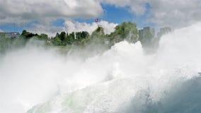 Μια όμορφη άποψη μιας ροής, ισχυρός καταρράκτης, στο υπόβαθρο που κυματίζει τη σημαία της Ελβετίας Καταρράκτης στον ποταμό RH φιλμ μικρού μήκους