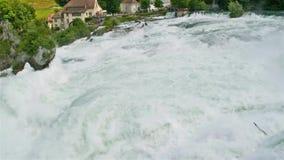 Μια όμορφη άποψη μιας ροής, ισχυρός καταρράκτης, στο υπόβαθρο που κυματίζει τη σημαία της Ελβετίας Καταρράκτης στον ποταμό RH απόθεμα βίντεο