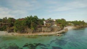 Μια όμορφη ανοικτό πράσινο ακτή με τους σκοπέλους και ένα αγαπώντας ζεύγος στο μπαλκόνι επάνω από την παραλία Η όμορφη φύση απόθεμα βίντεο