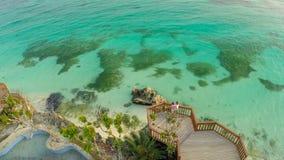 Μια όμορφη ανοικτό πράσινο ακτή με τους σκοπέλους και ένα αγαπώντας ζεύγος στο μπαλκόνι επάνω από την παραλία Η όμορφη φύση Στοκ φωτογραφία με δικαίωμα ελεύθερης χρήσης