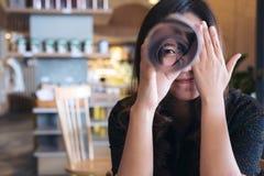 Μια όμορφη ασιατική γυναίκα κυλά ένα βιβλίο και το κοίταγμα μέσω του με ένα μάτι κλείνοντας ένα άλλο μάτι με το αίσθημα ευτυχής Στοκ φωτογραφίες με δικαίωμα ελεύθερης χρήσης