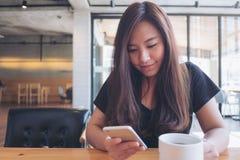 Μια όμορφη ασιατική γυναίκα με το πρόσωπο smiley που κρατά και που χρησιμοποιεί το έξυπνο τηλέφωνο με το άσπρο φλυτζάνι καφέ στον στοκ φωτογραφία με δικαίωμα ελεύθερης χρήσης