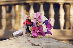 Μια όμορφη γαμήλια ανθοδέσμη που βρίσκεται σε μια πέτρα πέρα από το παλαιό σπίτι Στοκ Εικόνα