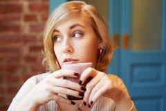 Μια όμορφη γυναίκα με τα σύντομα ξανθά μαλλιά και τα μπλε μάτια φαίνεται έξω το παράθυρο στοκ φωτογραφία με δικαίωμα ελεύθερης χρήσης