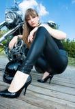 Μια όμορφη γυναίκα πλησίον με τη μοτοσικλέτα στοκ φωτογραφίες με δικαίωμα ελεύθερης χρήσης