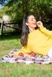 Μια όμορφη γυναίκα που τρώει τη Apple στον κήπο το φθινόπωρο Στοκ εικόνες με δικαίωμα ελεύθερης χρήσης