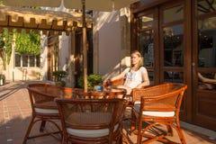 Μια όμορφη γυναίκα σε ένα άσπρο πουκάμισο γραμμάτων Τ, κάθεται στον καφέ Στην οδό στοκ εικόνα με δικαίωμα ελεύθερης χρήσης