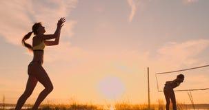 Μια όμορφη γυναίκα σε ένα μπικίνι με μια σφαίρα στο ηλιοβασίλεμα παίρνει έτοιμη να κάνει εξυπηρετεί το άλμα στην παραλία σε μια α απόθεμα βίντεο