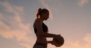 Μια όμορφη γυναίκα σε ένα μπικίνι με μια σφαίρα στο ηλιοβασίλεμα παίρνει έτοιμη να κάνει εξυπηρετεί το άλμα στην παραλία σε μια α φιλμ μικρού μήκους