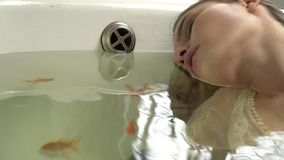 Μια όμορφη γυναίκα σε ένα nightie εναπόκειται στις προσοχές της ιδιαίτερες στην μπανιέρα και επιπλέει γύρω από τα ψάρια φιλμ μικρού μήκους