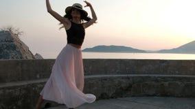 Μια όμορφη γυναίκα στα υψηλά τακούνια και σε ένα ελαφρύ φόρεμα χορεύει χαριτωμένα με ένα καπέλο στην πλατφόρμα απόθεμα βίντεο