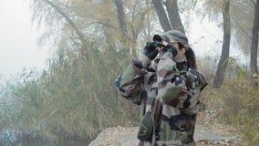 Μια όμορφη γυναίκα στην κάλυψη στρατού εξετάζει τα περίχωρα με τις διόπτρες που στέκονται στην όχθη ποταμού σε έναν ομιχλώδη απόθεμα βίντεο