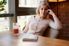 Μια όμορφη γυναίκα συγγραφέων έκλινε τον αγκώνα της σε μια καρέκλα, εξετάζοντας τη κάμερα με ένα ευχάριστο βλέμμα στοκ φωτογραφία με δικαίωμα ελεύθερης χρήσης