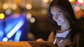 Μια όμορφη γυναίκα brunette, που χαμογελά, χρησιμοποιώντας την ταμπλέτα της Πόλη νύχτας, θολωμένα φω'τα στο υπόβαθρο, αργό MO απόθεμα βίντεο