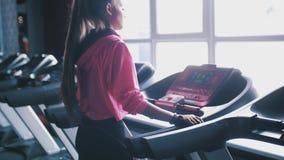 Μια όμορφη καυκάσια γυναίκα που τρέχει σε μια γυμναστική treadmill απόθεμα βίντεο