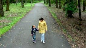 Μια όμορφη μητέρα και η χαριτωμένη μικρή κόρη της που περπατούν στο πάρκο απόθεμα βίντεο