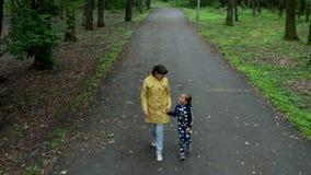 Μια όμορφη μητέρα και η χαριτωμένη μικρή κόρη της που περπατούν στο πάρκο φιλμ μικρού μήκους