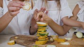 Μια όμορφη μητέρα με δύο παιδιά στα άσπρα ενδύματα κάνει μια πυραμίδα των τεμαχισμένων κίτρινων και πράσινων κολοκυθιών στην κουζ απόθεμα βίντεο