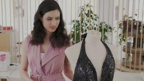 Μια όμορφη μοδίστρα περπατά γύρω από ένα μανεκέν με ένα καθιερώνον τη μόδα φόρεμα βραδιού Σκοτεινό λαμπρό φόρεμα με ένα βαθύ ύφασ φιλμ μικρού μήκους