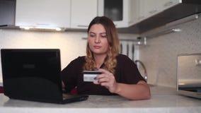 Μια όμορφη νέα γυναίκα αγοράζει on-line να χρησιμοποιήσει ένα lap-top και μια τεμαχισμένη κάρτα Εγχώριο ύφος φιλμ μικρού μήκους
