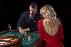 Μια όμορφη νέα γυναίκα και ένας άνδρας κάθονται σε έναν πίνακα ρουλετών casino Στοκ εικόνα με δικαίωμα ελεύθερης χρήσης