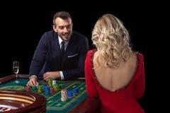 Μια όμορφη νέα γυναίκα και ένας άνδρας κάθονται σε έναν πίνακα ρουλετών casino Στοκ Εικόνες