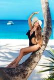 Μια όμορφη νέα γυναίκα με μακρυμάλλη σε ένα καπέλο αχύρου χαλαρώνει επάνω στοκ εικόνα