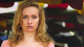 Μια όμορφη νέα γυναίκα με τα ξανθά μαλλιά στέκεται σε έναν ανοιχτό χώρο μια θυελλώδη ημέρα εξετάζοντας με προσήλωση τη κάμερα αντ απόθεμα βίντεο