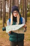 Μια όμορφη νέα γυναίκα με το χάρτη ταξιδιού και σακίδιο πλάτης στις φυτείες πεύκων Στοκ φωτογραφία με δικαίωμα ελεύθερης χρήσης