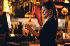 Μια όμορφη νέα γυναίκα στο γραφείο σε ένα εστιατόριο στοκ εικόνα
