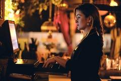 Μια όμορφη νέα γυναίκα στο γραφείο σε ένα εστιατόριο στοκ φωτογραφία