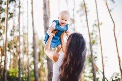 : Μια όμορφη νέα καυκάσια μαμά γυναικών κρατά σε ετοιμότητα της, ρίχνει επάνω στους ανελκυστήρες σε ετοιμότητα της επάνω στην κόρ στοκ φωτογραφίες