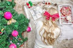 Μια όμορφη νέα ξανθή γυναίκα, με ένα τόξο στο κεφάλι της, βρίσκεται στο πάτωμα και τυλίγει τα δώρα Χριστουγέννων r Ευπρέπειες στοκ φωτογραφία