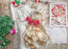 Μια όμορφη νέα ξανθή γυναίκα, με ένα τόξο στο κεφάλι της, βρίσκεται στο πάτωμα και τυλίγει τα δώρα Χριστουγέννων r Ευπρέπειες στοκ φωτογραφία με δικαίωμα ελεύθερης χρήσης