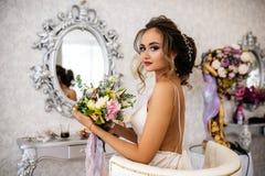 Μια όμορφη νύφη με μια γαμήλια ανθοδέσμη στα χέρια της κάθεται σε μια καρέκλα, εξετάζει τη κάμερα Στοκ Εικόνες