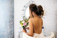 Μια όμορφη νύφη με μια γαμήλια ανθοδέσμη στα χέρια της κάθεται σε μια καρέκλα, πίσω άποψη Στοκ Εικόνα