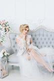 Μια όμορφη νύφη σε μια ρόμπα κάθεται στον καναπέ eligantly Στοκ Εικόνες