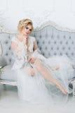 Μια όμορφη νύφη σε μια ρόμπα κάθεται στον καναπέ eligantly Στοκ Εικόνα