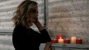 Μια όμορφη ξανθή γυναίκα σε ένα μαύρο φόρεμα πλησιάζει το ράφι με το κάψιμο των κεριών και τους εκρήγνυται Αναμονή  απόθεμα βίντεο