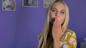 Μια όμορφη ξανθή γυναίκα χαμογελά και φυσά ένα φιλί απόθεμα βίντεο