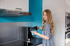 Μια όμορφη ξανθή γυναίκα χύνει τον καφέ από τον κατασκευαστή καφέ σε ένα φλυτζάνι Στοκ Εικόνες
