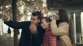 Μια όμορφη οικογένεια selfie το βράδυ στις οδούς πόλεων με τα φω'τα απόθεμα βίντεο