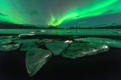 Μια όμορφη πράσινη και κόκκινη αυγή που χορεύει άνω του Λα Jokulsarlon Στοκ Εικόνες