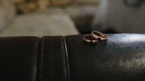 Μια όμορφη πτήση της κάμερας στα γαμήλια δαχτυλίδια που βρίσκονται στον καναπέ δέρματος απόθεμα βίντεο