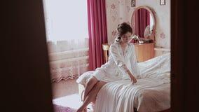 Μια όμορφη συνεδρίαση κοριτσιών σε ένα κρεβάτι αγγίζει ένα φόρεμα και το ισιώνει απόθεμα βίντεο