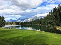 Μια όμορφη τρύπα γκολφ στην ιάσπιδα, Αλμπέρτα, υψηλή στα δύσκολα βουνά βουνών Η στενή δίοδος είναι εκτός από μια όμορφη λίμνη στοκ φωτογραφία με δικαίωμα ελεύθερης χρήσης