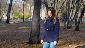 Μια όμορφη χαμογελώντας γυναίκα στέκεται στο πάρκο φθινοπώρου 4k 60fps Κορίτσι σε ένα παλτό που περπατά στο πάρκο πόλεων φθινοπώρ απόθεμα βίντεο