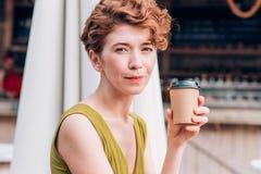 Μια όμορφη redhead γυναίκα σε ένα φόρεμα που κρατά έναν καφέ και που εξετάζει τη κάμερα, κινηματογράφηση σε πρώτο πλάνο Στοκ Φωτογραφίες