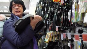 Μια ώριμη γυναίκα επιλέγει ένα τηγανίζοντας τηγάνι χυτοσιδήρων στην υπεραγορά
